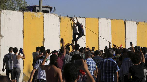 Protesters climb the blast walls surrounding Baghdad's highly fortified Green Zone (AP)