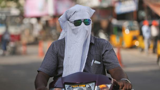 A man rides a scooter with his face covered with a cloth to protect him from a heat wave in Hyderabad, India (AP)