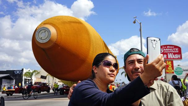 A space shuttle external fuel tank, the last one in existence, moves past on a street in Inglewood, California
