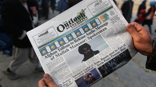A local Afghan newspaper with photos of the leader of the country's Taliban, Mullah Mansour, dated December 2015 (AP)