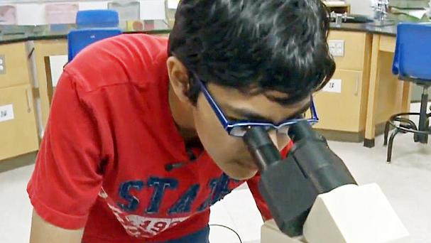 Tanishq looks into a microscope in a lab at American River College in Sacramento (KOVR-TV/AP)