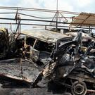 Syrians look at the remains of burned vehicles at the site of a bombing in the coastal towns of Tartus (SANA via AP)