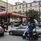 Drivers queue to buy petrol in a station, in Paris (AP)