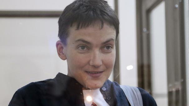 Nadezhda Savchenko smiles to journalists from a glass cage in court, in Donetsk. The Ukrainian pilot has been freed by Russia in a prisoner swap (AP)