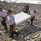 French police carry a piece of debris from a plane in Saint-Andre, Reunion Island (AP)