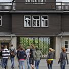 Visitors walk in front of the entrance building in the former Nazi concentration camp Buchenwald near Weimar, Germany (AP)