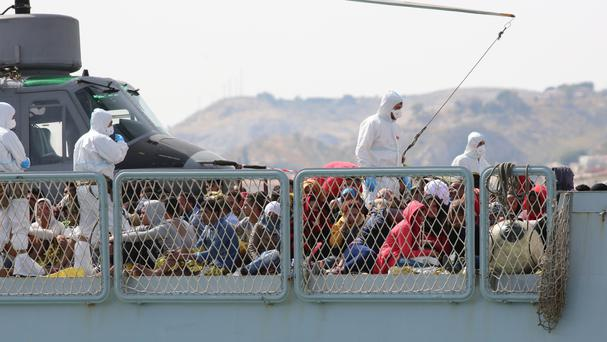 Migrants wait to disembark from the Italian Navy ship Bettica as it arrives at the Sicilian Porto Empedocle harbour (AP)