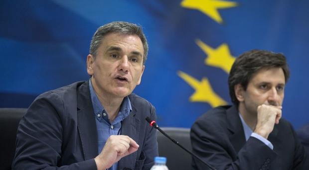Greek Finance Minister, Euclid Tsakalotos, left speaks next to deputy Finance Minister Giorgos Houliarakis (AP)