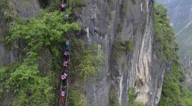 Children wearing their school backpacks climb on a cliff on their way home from school in Zhaojue county (AP)