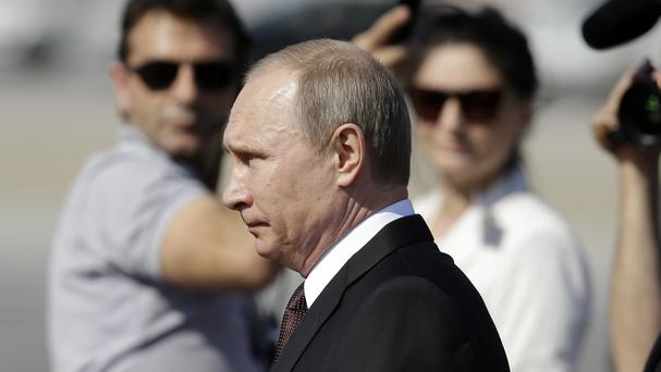 Russian President Vladimir Putin inspects the honour guard during his arrival at the Athens international airport (AP)