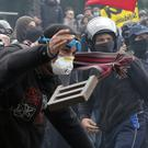 Protesters throw objects at police during a demonstration against labour reforms in Paris (AP)