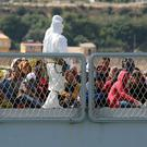 Migrants wait to disembark from an Italian navy ship (AP)