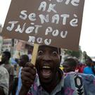 "A supporter of presidential candidate Jovenel Moise holds up a sign with a message that reads in Creole ""Deputies and senators the responsibility is yours"" (AP)"