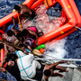 Rescuers help migrants to board the Italian Navy ship Vega, after the boat they were aboard sunk. The Italian navy says it saved 135 people from the boat and recovered 45 bodies. Photo: AP