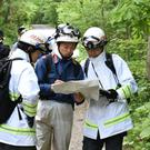 Rescuers search for a seven-year-old boy who is missing in a Japanese forest on Hokkaido (Kyodo News/AP)
