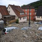 Cars are covered in rubble on a street in Braunsbach, south-western Germany (Marijan Murat/dpa via AP)