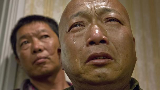 Ma Wenyi, whose father was one of thousands forced to work during the Second World War for Mitsubishi Mining, cries in Beijing (AP)
