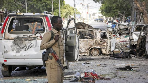 A Somali policeman patrols at the scene after a bomb attack on Ambassador Hotel in Mogadishu (AP)