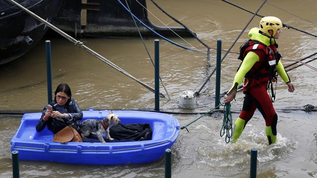 A fireman pulls a woman and her dog to shore by a row of houseboats on the River Seine in Paris (AP)