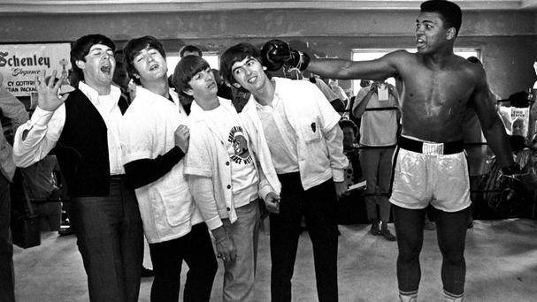 The Beatles take a fake blow from Cassius Clay, later Muhammad Ali, in 1964 at his training camp in Miami Beach (AP)