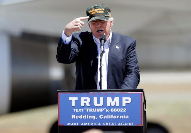 Donald Trump gestures to a his camouflaged 'Make America Great' hat as he discusses his support by the National Rifle Association at a campaign rally in Redding, California Photo: Rich Pedroncelli/AP