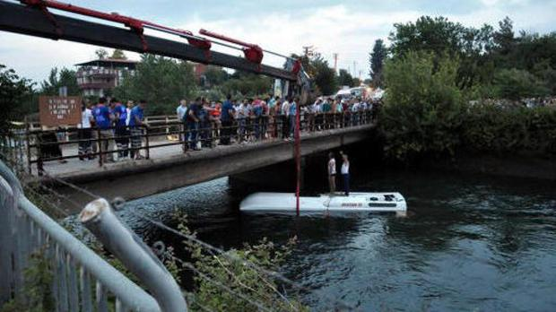 Turkish rescuers lift a bus from a canal near Osmaniye, Turkey (DHA via AP)