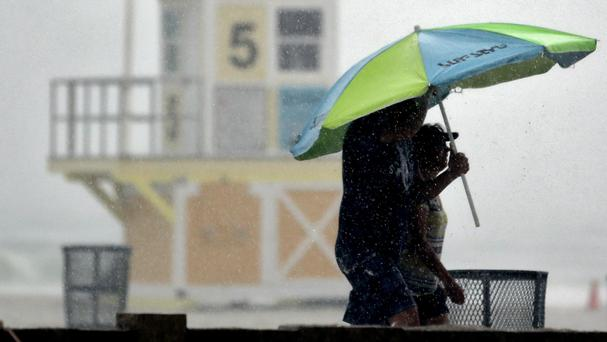 Beachgoers take shelter under an umbrella after a sudden downpour associated with Storm Colin came ashore at Clearwater Beach (AP)