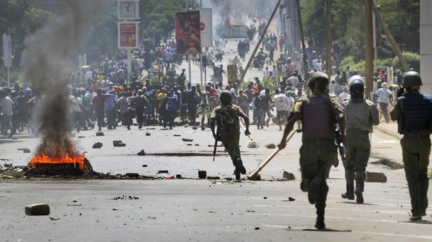 Riot police chase protesters calling for the disbandment of the national electoral commission (AP)