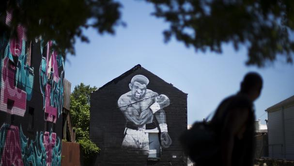 A pedestrian passes a mural of Muhammad Ali painted on the side of a building in Louisville, Kentucky (AP)