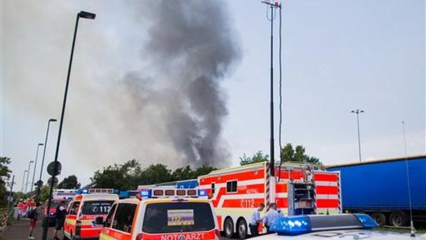 Rescue cars stand near refugee accommodation where a fire broke out in Duesseldorf (Rolf Vennenbernd/dpa via AP)