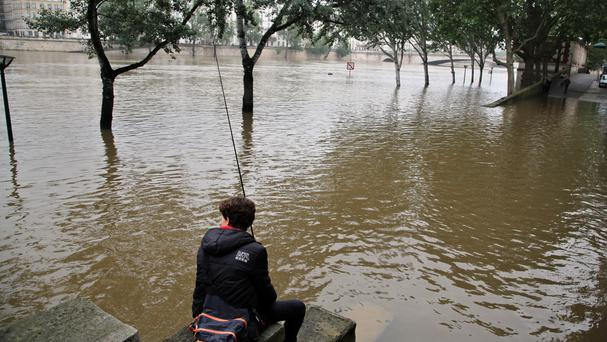 A boy fishes in the Seine river during floods in Paris (AP)