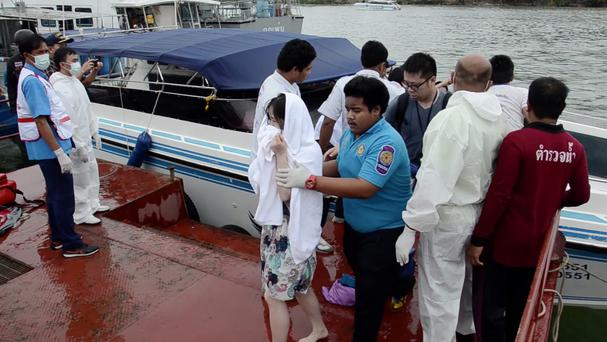 A passenger is assisted from a police rescue boat at a pier in Phuket, Thailand (AP)