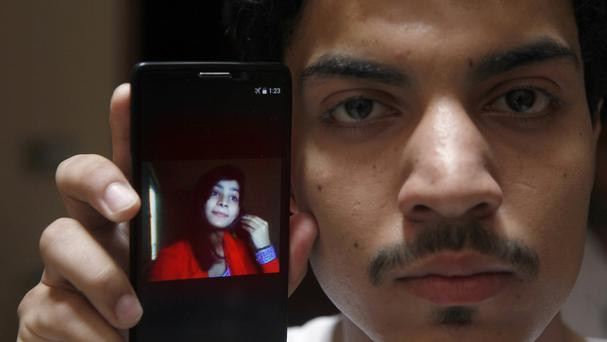 Hassan Khan shows the picture of his wife Zeenat Rafiq on a mobile phone at his home in Lahore, Pakistan (AP)