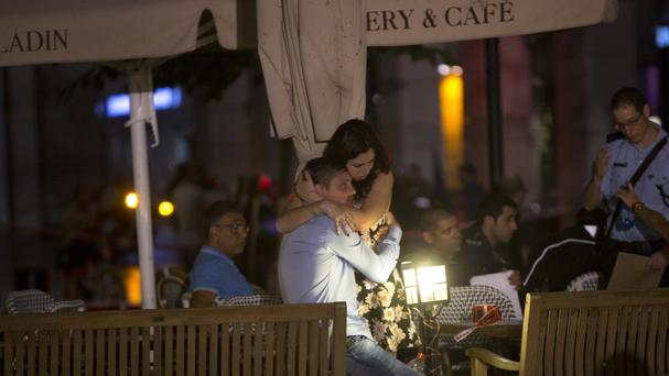 People console each other near the scene of a shooting in Tel Aviv (AP)