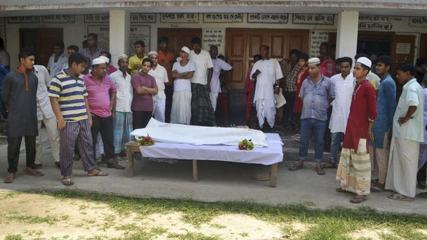 Locals surround the body of a Hindu holy man after assailants hacked him to death in Pabna (AP)