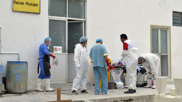 Forensic workers suit up as they continue the post-mortems of 11 family members at a morgue in Tehuacan (AP)