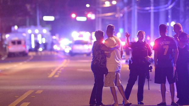 Orlando Police officers direct family members away from a multiple shooting at a nightclub (AP)