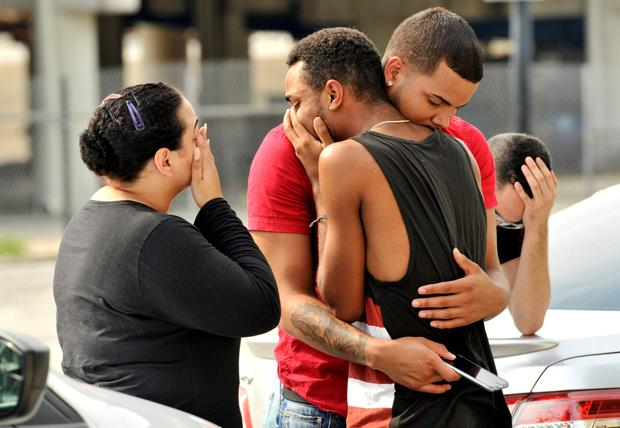 Friends and family members embrace outside the Orlando Police Headquarters during the investigation of a shooting at the Pulse night club. Photo: Reuters