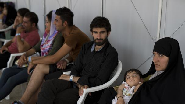 Afghan migrants who live in the Hellenikon refugee and migrant camp (AP)
