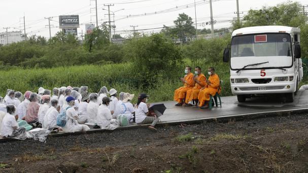 Buddhist monks and devotees block a road outside the Wat Dhammakaya temple (AP)