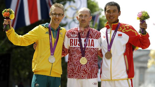 Jared Tallent of Australia stands with Sergei Kirdyapkin of Russia and Si Tianfeng of China on the Olympics medals podium after the men's 50k race walk competition at London 2012 (AP)