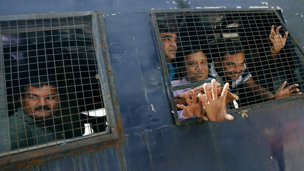 A police van carries some of those who were convicted to jail (AP)