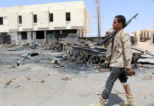 An armed guard walks past the remains of a burnt truck after a suicide car bomber attacked a Libyan police station west of Sirte this week. Photo: Reuters