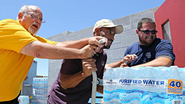 A shipment of 20,000 water bottles arrives at a homeless shelter in Phoenix (AP)