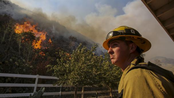A firefighter keeps watch a wildfire in Azusa, California (AP)