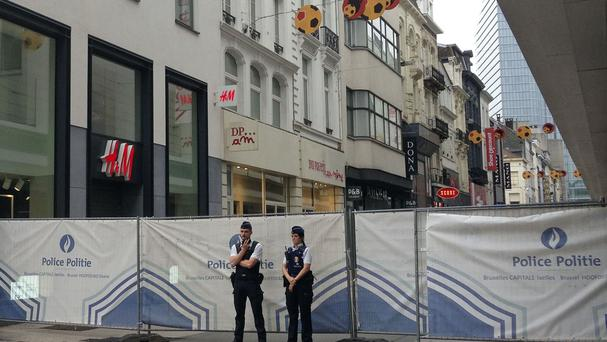 Police officers stand guard near a blocked-off street in Brussels after Belgian authorities took a man into custody following a pre-dawn security alert at a major shopping centre (AP)