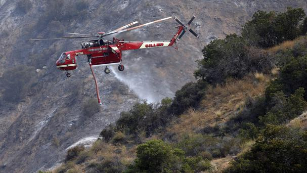 A firefighting helicopter makes a water drop on a hill near a wildfire in Duarte, California (AP)