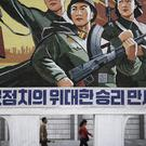 "A North Korean man and woman walk under a mural with a message which reads ""Long live the great victory of the army-first policy"" (AP)"