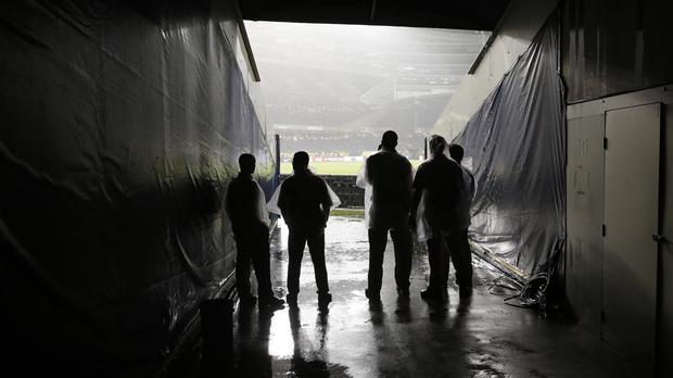 Stadium personnel watch the rain from the tunnel during the Copa America semi-final between Chile and Colombia at Soldier Field in Chicago (AP)