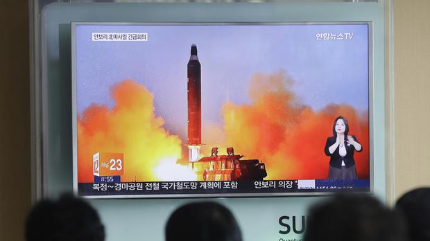People watch a TV news channel airing an image of North Korea's ballistic missile launch (AP)